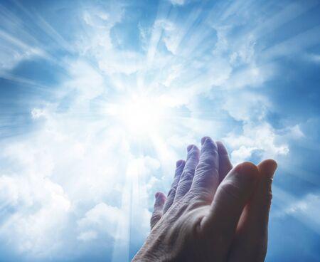 cielo: Las manos juntas orando en el cielo brillante