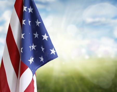 青と緑の背景の前でアメリカの国旗