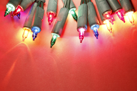 multiple objects: Closeup of Christmas lights glowing on red background Stock Photo