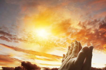 cristianismo: Hands together praying in bright sky Foto de archivo