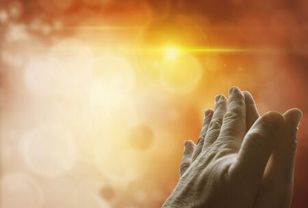 Hands together praying in front of bright background. Copy space Stock Photo
