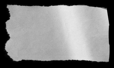 Piece of torn paper on black Banque d'images