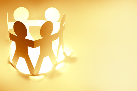 Team of paper chain people holding hands. Copy space Stock Photo