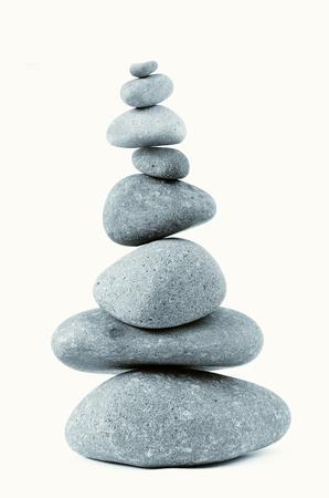 Pile of balanced rocks on plain background