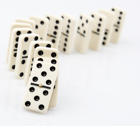 Dominoes on plain background, about to fall Stock Photo
