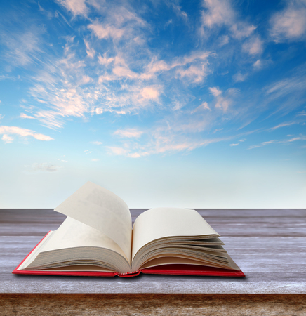 Open book on table in front of sky