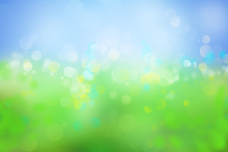 Blurry green meadow and blue sky spring background Imagens