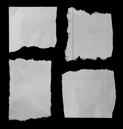 Quatre morceaux de journal déchiré sur fond noir