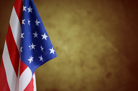 American flag in front of brown background.