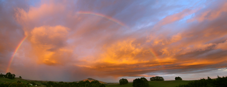 Rainbow in sunset sky over New Zealand landscape