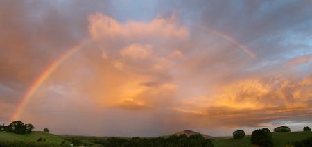 Rainbow in sunset sky over New Zealand landscape