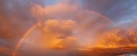 Rainbow in orange clouds sky Imagens