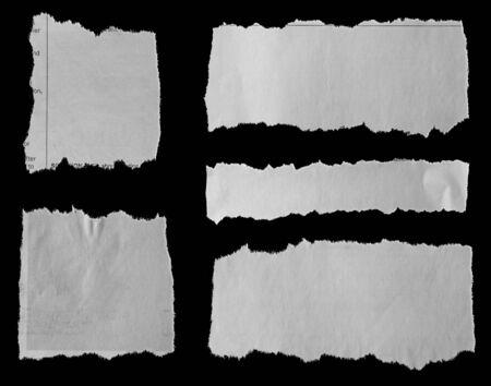 Cinq morceaux de journal déchiré sur fond noir