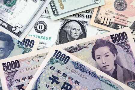Close-up of assorted American and Yen banknotes overlapping