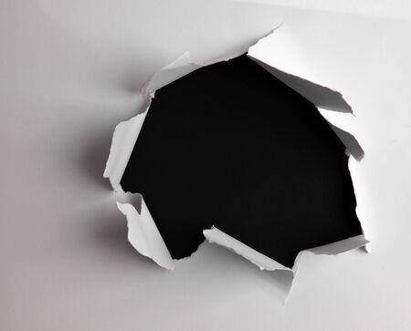 Buco strappato in carta su nero Archivio Fotografico