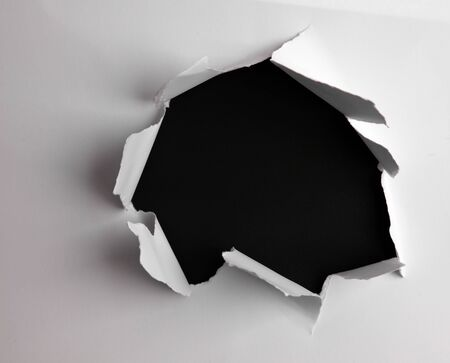 Hole ripped in paper on black