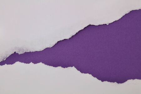 Hole ripped in paper on purple background
