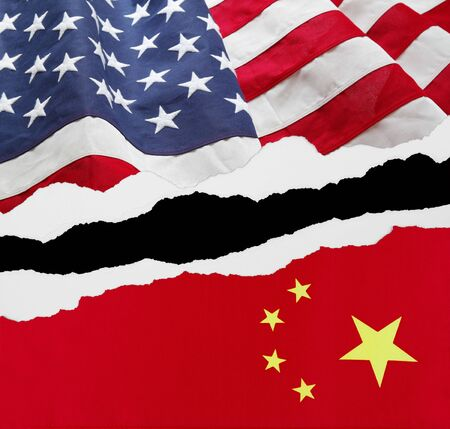 American and China flags torn apart on black background