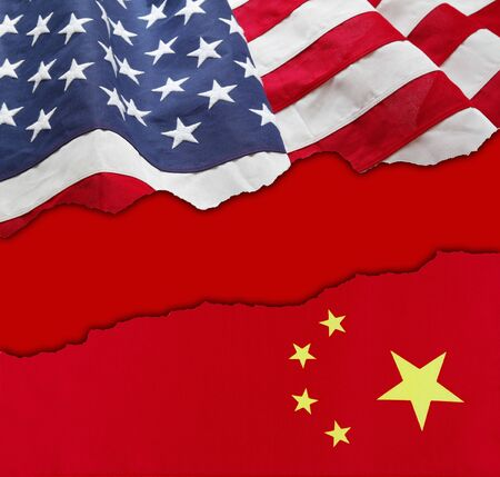 American and China flags torn apart on red background 写真素材