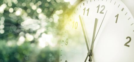 Clock and green blurred background. Spring time 写真素材