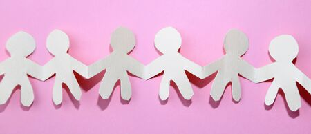 Team of paper chain cutout people in a row on pink background holding hands 写真素材 - 132126533