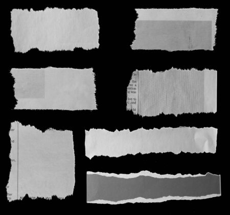 Seven pieces of torn newspaper on black background 写真素材
