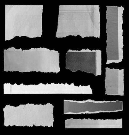 Ten pieces of torn newspaper on black background 写真素材
