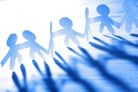 Squadra di persone a catena di carta che si tengono per mano. Tono blu. Lavoro di squadra. Collaborazione.