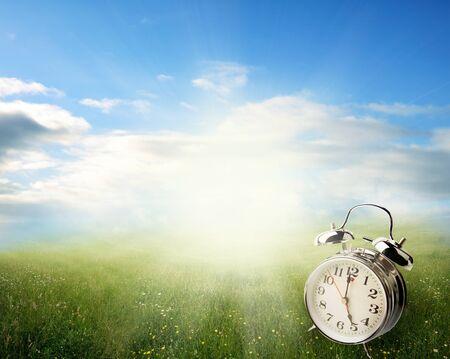 Despertador en campo de primavera iluminado por el sol Foto de archivo