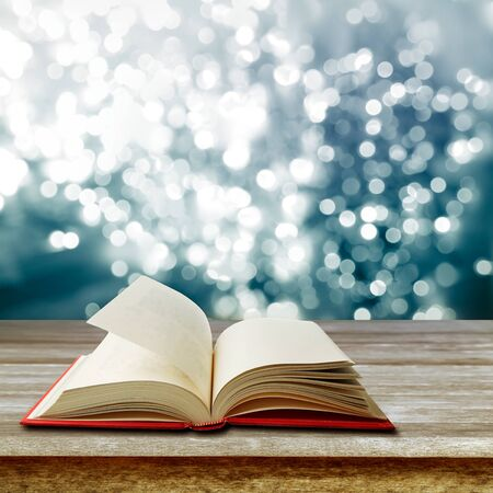 Open book on table in front of bright lights