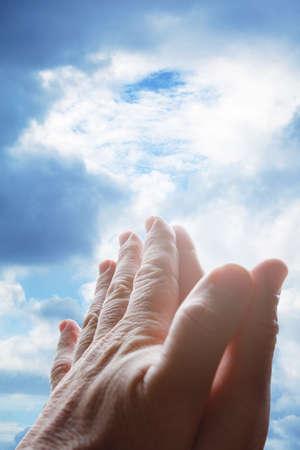 Hands praying in the sky 版權商用圖片