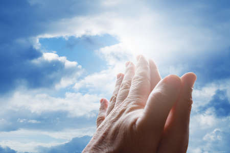 Hands praying in the sky