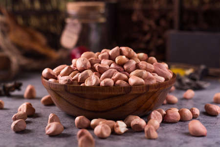 arachis: close up of raw peanuts or arachis in ceramic bowl on wood background Stock Photo