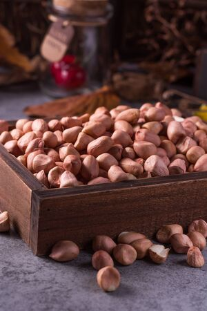 earthnuts: close up of raw peanuts or arachis in ceramic bowl on wood background Stock Photo