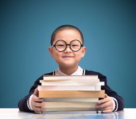 ni�os estudiando: un ni�o sostener el libro Foto de archivo