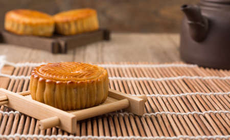 Mooncake and tea,food and drink for Chinese mid autumn festival. Traditional mooncakes on table setting with teapot.