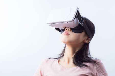 Woman in VR headset looking up at the objects Stock Photo
