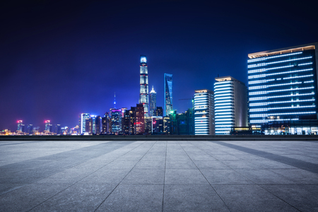 Empty floor with modern skyline and buildings at night in Shanghai