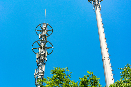 Red and white tower of communications with a lot of different antennas under blue sky and clouds Stock Photo