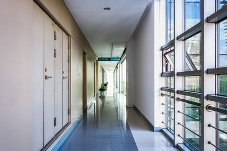 Long office hallway with a lot of yellow wooden doors. Banque d'images