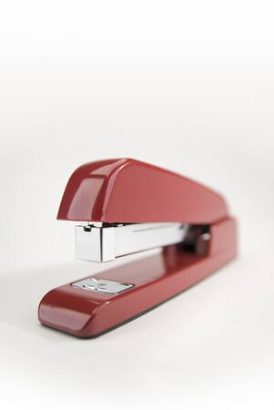 verticals: Close-up image of a red stapler on a white background.