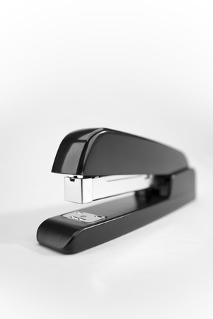 verticals: Close-up image of a black stapler on a white background. Stock Photo