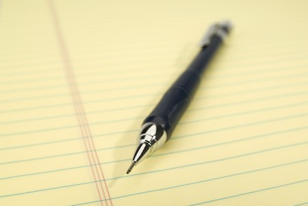 legal pad: Blue mechanical pencil on a yellow legal pad. Focus on the tip of the pencil.