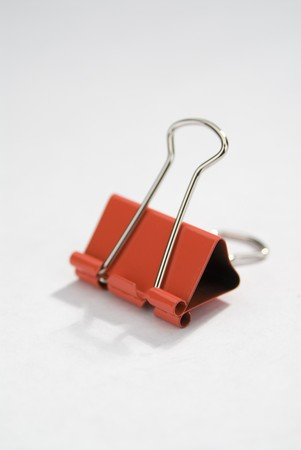 verticals: Red binder clip on a white background.