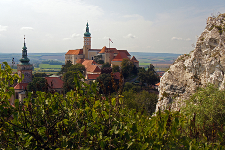 Castle and the church behind the leafs of trees and rocks. Made in the sunny summer day. Touristic destination in Central Europe
