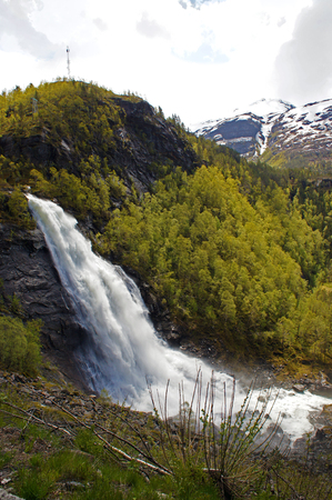 Fossen Bratte waterfall in Samnanger, Hordaland, Norway surrounded by mountains Stock Photo