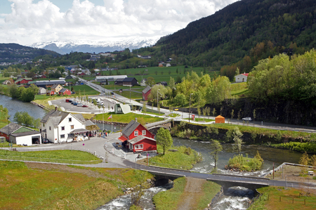 View from Steinsdalsfossen waterfall in the river of steine ??- scenic landscape with cascade surounded by mountains and traditional norwegian, scandinavian houses Stock Photo