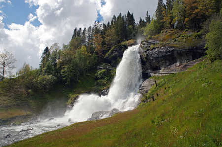 Steinsdalsfossen waterfall in the river of steine ??- scenic landscape with cascade surounded by mountains and traditional norwegian, scandinavian houses