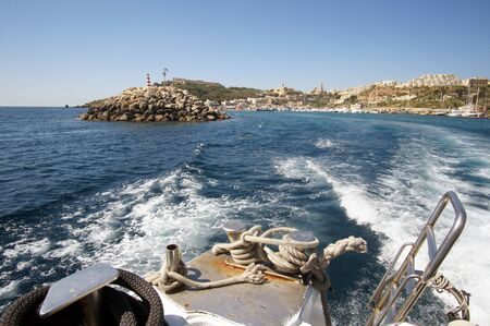 Landscape of Mgarr Harbor in Gozo, Malta visible from antique yacht deck