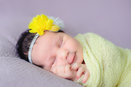 A cute newborn with a head strap sleeping in his bad Imagens